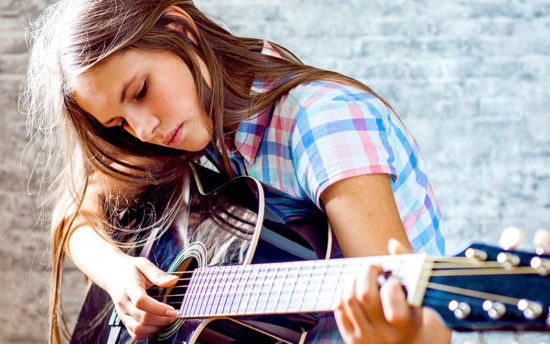 Young girl playing guitar.