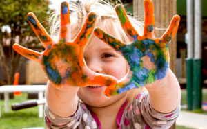 Young child excitedly holding up painted hands.
