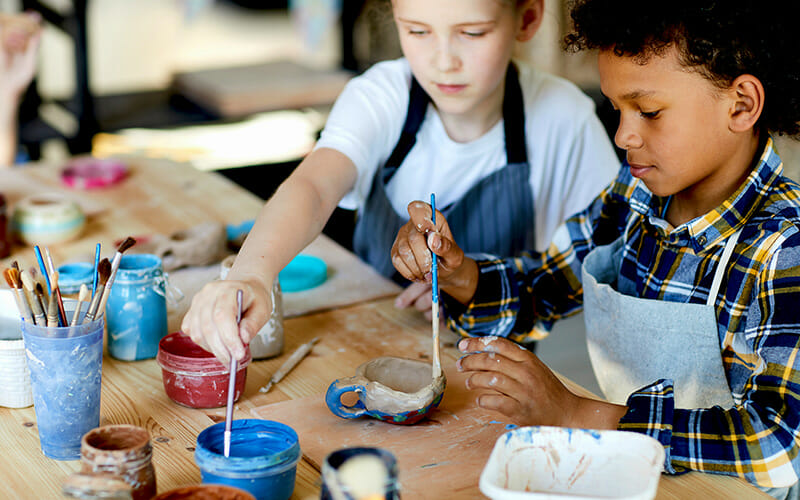 Two youthful children sitting by table painting self-made clay project.