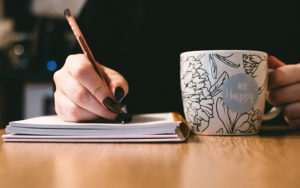 Adult writing stories while holding a white, painted ceramic mug.