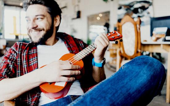 Adult male playing the ukulele