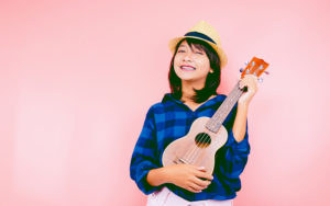 young girl playing a ukulele