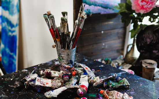 table covered with paint brushes and tubes of oil paints