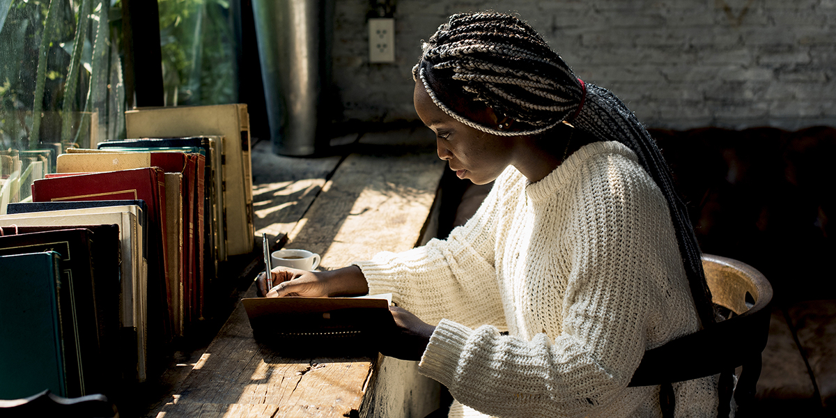 African American woman writing in a journal