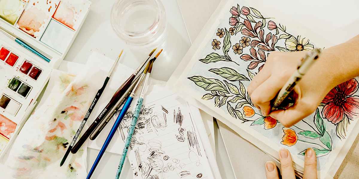image of someone working on a visual journal in watercolors